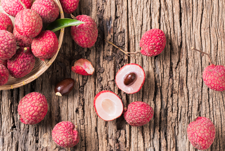 sliced fresh organic lychee fruit on old wood background.