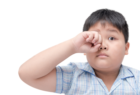 Obese boy itchy his eyes because dust in eye, Health care concept..