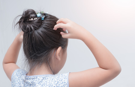discomfort: little girl hand itchy scalp on gray background, Hair care concept. Stock Photo