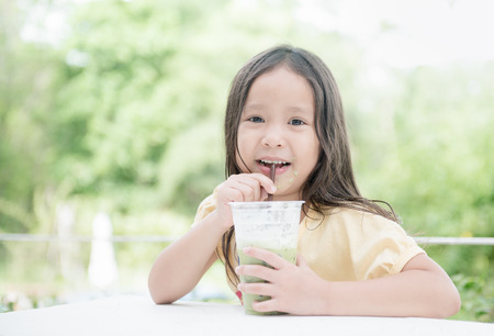 cute asian girl drinking ice milk green tea on nature background..