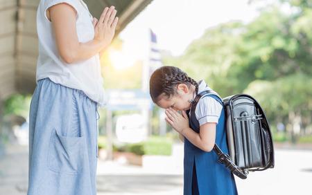 かわいい女の子の学生は、学校に行く前に彼女の母親に敬意を払います。タイの文化。