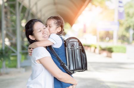 mother hug and kiss cute girl student before go to school, love and education concept. Stockfoto