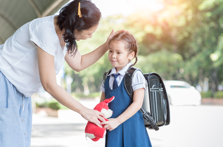 Mother standing at school holding hands and teaching her daughter, love concept. Archivio Fotografico