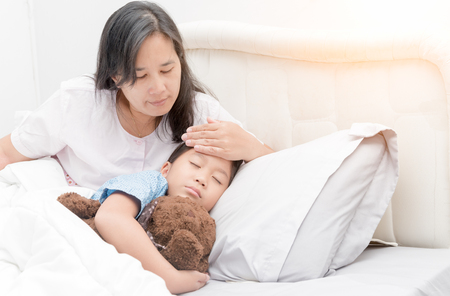 Sick girl laying in bed and mother hand taking temperature. Sick child with fever and illness in bed, healthcare concept. Banque d'images