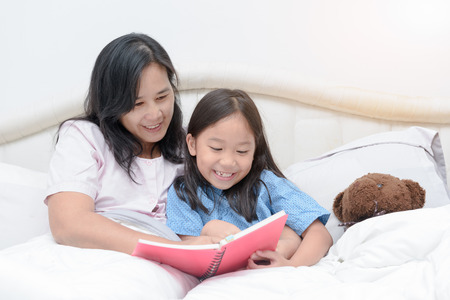 Mother and daughter reading book on bed, concept education