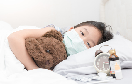 Sick girl with hygienic mask laying on bed, healthy concept. Stockfoto