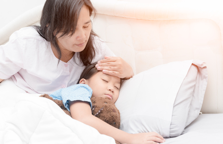 침대 및 어머니 손 복용 온도에 누워 아픈 소녀. 발열과 병, 침대, 건강 관리 개념에 아픈 아이. 스톡 콘텐츠
