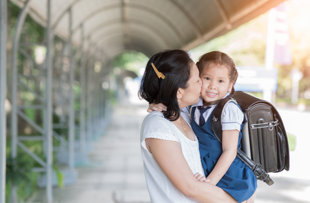 Moeder die schoolmeisje in eenvormig vóór het gaan naar school, Liefde en zorgconcept kussen. Stockfoto