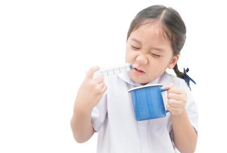 鼻を洗ってください。アジアの学生の女の子が注射器と白い背景で隔離の生理食塩水鼻をフラッシュします。