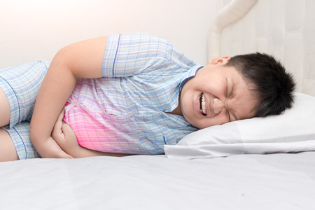 asian fat child suffering from stomachache and red spot indicating location of pain. healthy concept.