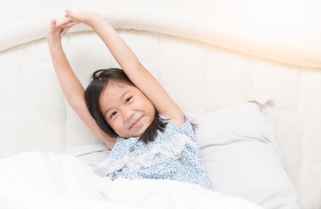 パジャマかわいいアジアの女の子は、伸縮ベッドに座っています。おはよう世界。