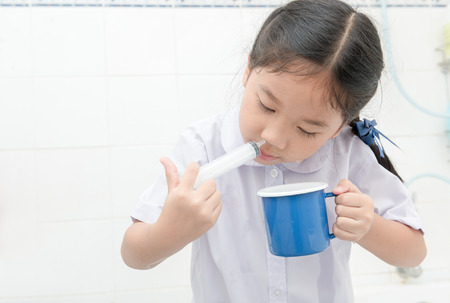 Neuswas. Aziatische student meisje spoelen haar neus met spuit en zoutoplossing in de badkamer, Sinus Behandeling en gezondheidszorg concept. Stockfoto