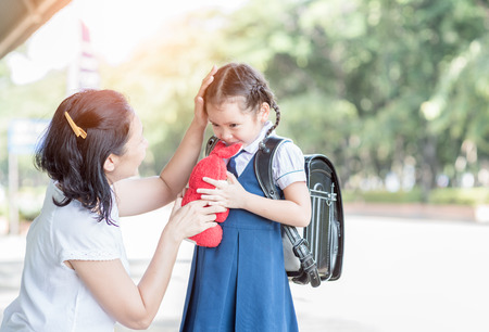 Mother standing at school holding hands and teaching her daughter, love concept .