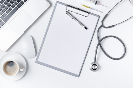 Top view of doctor desk table with stethoscope, coffee  and blank paper on clipboard with pen. Top view with copy space, flat lay..