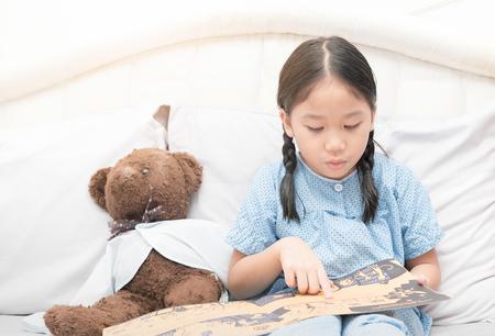 침대, 교육 개념에 동화 책을 읽고 귀여운 작은 아시아 소녀.
