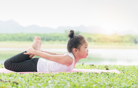 Happy cute girl playing gymnastic on outdoor park, exercise and healthy concept Stock Photo