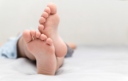 little girl's feet who sleeps in her bed closeup, comfort and relaxation concept. Stockfoto