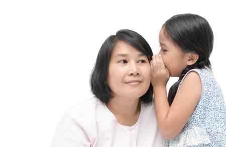 娘は白い背景、信頼、愛、家族や母性の概念に分離された母親にゴシップをささやきます。