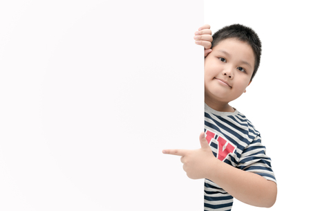 obese fat boy pointing on white banner board isolated on white background with copy space for input text. Banco de Imagens