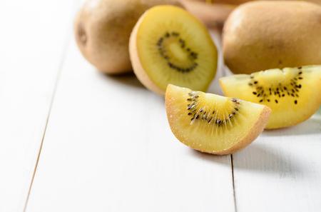 yellow or gold sliced kiwi fruit on white wood background, healthy fruits. Archivio Fotografico
