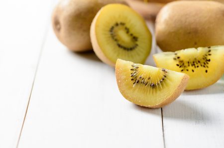 yellow or gold sliced kiwi fruit on white wood background, healthy fruits. Foto de archivo