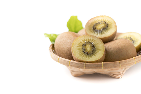 yellow or gold sliced kiwi fruit in basboo basket isolated on white wood background, healthy fruits.