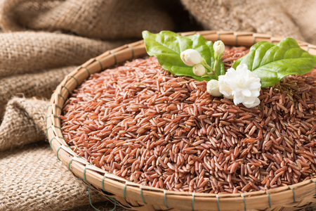 Jasmine brown rice beery  in bamboo basket on sack background, healthy food and diet concept..