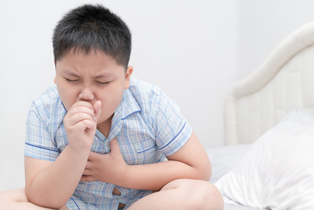 Sick obese boy is coughing and throat infection on bed, health care concept.