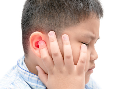 Obese fat boy touching his painful ear isolated on white background, health care concept.