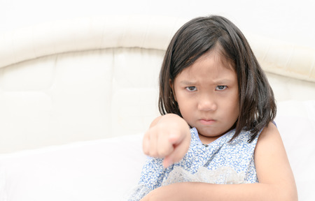 Blame, accusation. Portrait angry girl pointing finger at someone displeased on bed. Negative human face expressions and emotions concept. Stock Photo