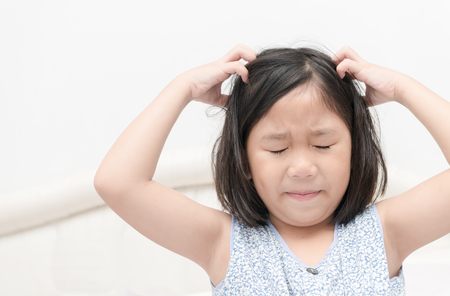 kid with freckles scratching his hair for head lice or allergies, Health care concept