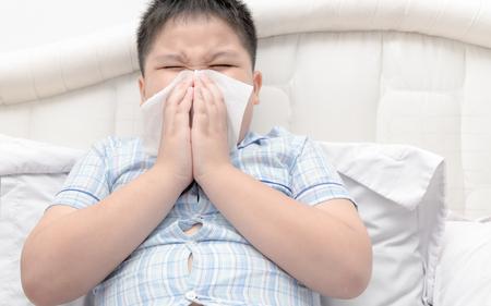 Flu. Obese boy got nose allergy, flu sneezing nose sitting on bed, health care concept