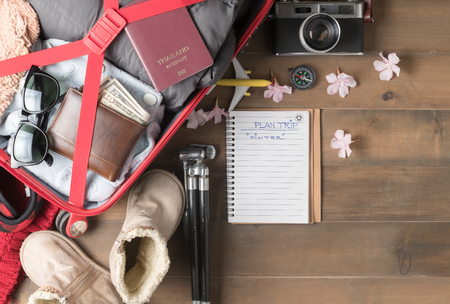 prepare winter trip and accessories travel items for on old wooden board, flat lay, top view background.
