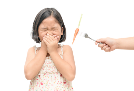 asian child girl with expression of disgust against vegetables isolated on white background, Refusing food concept.