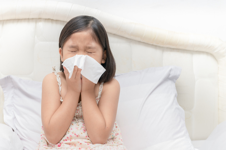 Asian girl blowing the nose by tissue, health care and sick concept.