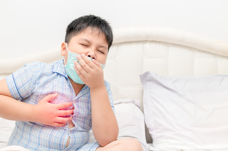Sick obese boy is coughing and throat infection on bed, health care concept..