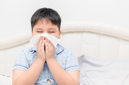 Asian obese fat boy blowing the nose by tissue, health care and sick concept.. Standard-Bild - 96998924