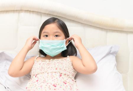 病気の女の子は、ベッドルーム、ヘルスケアと病気の子供の概念でインフルエンザウイルスから保護するために保護マスクを着用... 写真素材