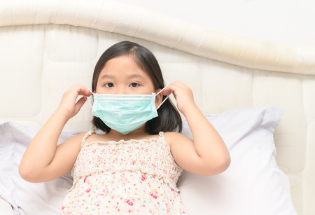 sick girl wear protection mask to protect against influenza virus in bed room, health care and sick child concept... 스톡 콘텐츠