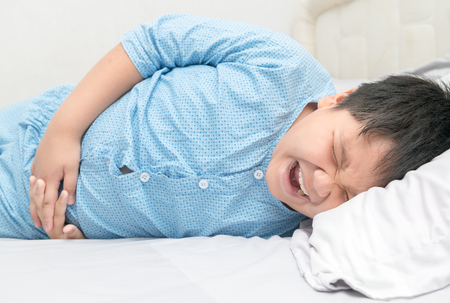asian child suffering from stomachache and lying on bed. diarrhea or healthy concept.