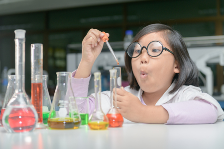 Excited little girl in lab coat making experiment with test tube in chemical laboratory, science and education concept.. 스톡 콘텐츠