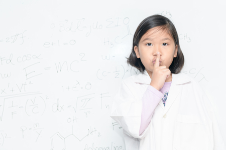 Scientist girl saying hush be quiet with finger on lips gesture on white borad with scientific equation, science and education concept.