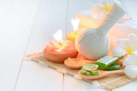 Herbal Compress and Aloe vera with candle on white wood background, ingredient spa concept..