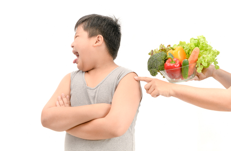 Obese fat boy with expression of disgust against vegetables isolated on white background, Refusing food concept.. Stock Photo