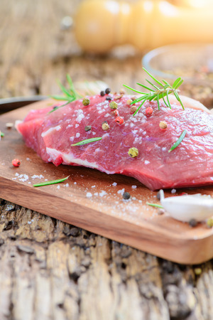 prepare fresh beef with salt garlic and rosemary leaf for beef steak on wood background. Stock Photo