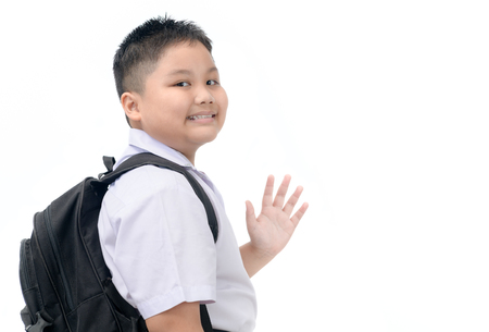Asian boy student going to school and waving goodbye isolated on white background, back to school conceptใ