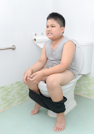 fat boy suffer stomach and sit in toilet, diarrhea constipation and health concept. Standard-Bild - 101802009