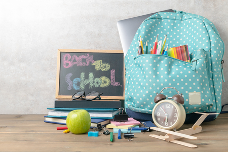 School backpack with coloured pencil and back to school text on blackboard on wood table background. Back to school concept.. Stok Fotoğraf