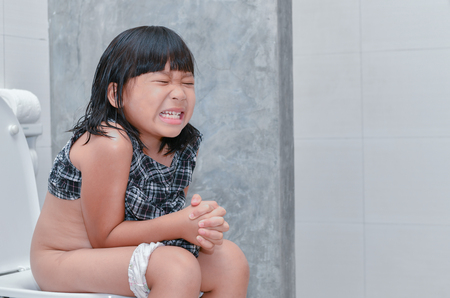 Little girl suffer stomach and sit in toilet, diarrhea constipation and health concept.