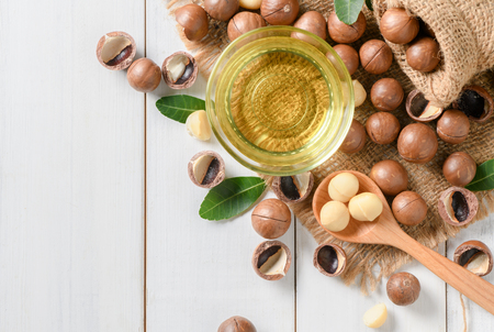 Bowl of macadamia nut oil and macadamia nuts on white wooden background. superfood and healthy food concept, top view.